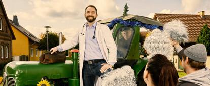 Landarzt wird mit einem Traktor auf den Dorfplatz gefahren. Die Dorfbewohner begrüßen ihn freudig.